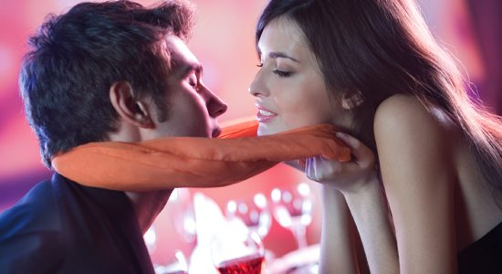 young couple kissing in restaurant, celebrating or on romantic d