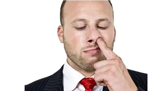 man digging his nose on isolated background