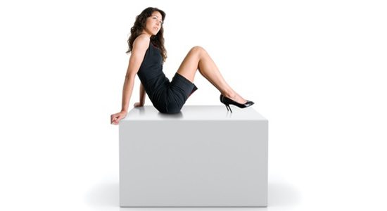Girl sitting on a gray cube