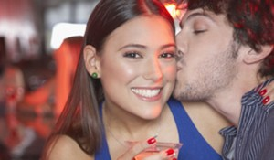 Couple in nightclub kissing and smiling