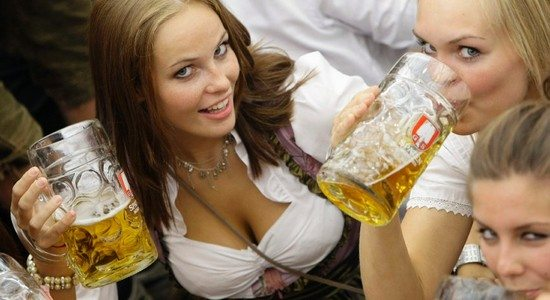 Women wearing  traditional Bavarian Dirndl pose with beer during 176th Oktoberfest in Munich